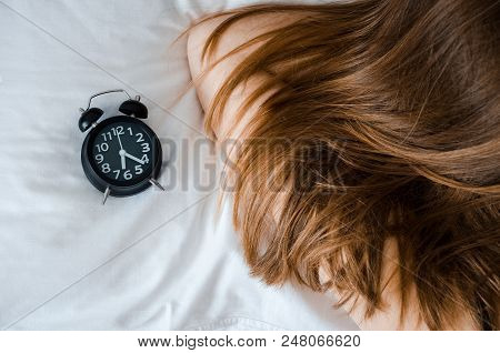 Young Woman Sleep With Alarm Clock On The Bed In The Morning. Unrecognizable Girl With Long Hair And