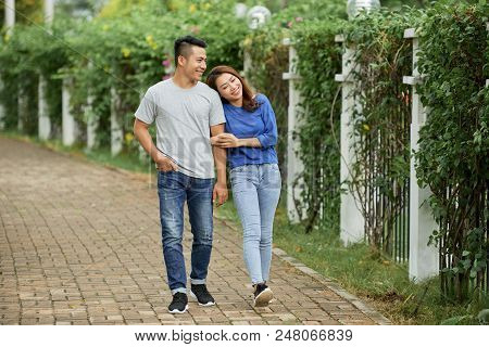 Loving Young Asian Couple Holding Hands And Walking On Pathway In Summer Green Park Being In Love