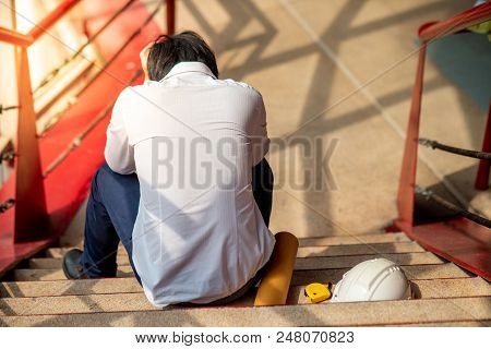 Engineer Or Architect Feeling Stressed, Worried And Tired With His Job While Sitting On Stair With P