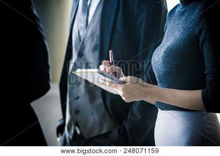 Hand Of Woman Holding Notebook For Working While Neeting Team. Woman Working Concept.