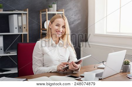 Cheerful Young Businesswoman Using Her Touchpad With Smile While Sitting At Her Working Place In Off