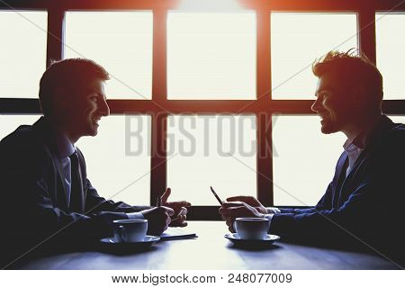 Two Businessmen Have Business Lunch With Cups Of Coffee In Cafe. Business Concepts. Discussion Of Fi