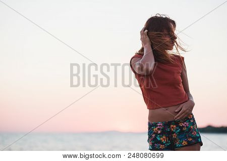 Young Woman Enjoying Sunset By The Sea