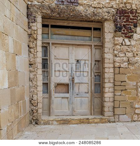 Facade Of Old Abandoned Weathered Wooden Door And Stone Bricks Wall