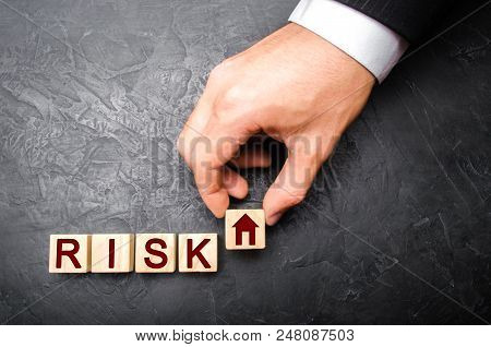 The realtor's hand stretches a cube with a house pattern to the word risk. The concept of risk, loss of real estate. Property insurance. Loans secured by home, apartment. Financial risks, litigation.