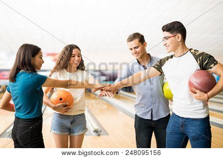 Smiling Teenage Girls And Boys Stacking Hands While Enjoying Bowling In Club