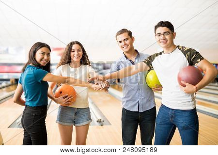Smiling Teen Friends Piling Hands At Bowling Alley In Club