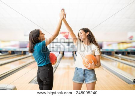 Teenage Girls Giving High-five Before Starting Bowling Game At Alley In Club