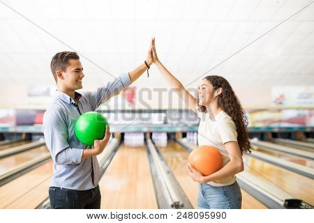 Male And Female Teenage Friends Showing Teamspirit With A High-five At Bowling Alley In Club