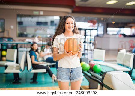 Teenage Girl Smiling While Enjoying Recreational Bowling In Club
