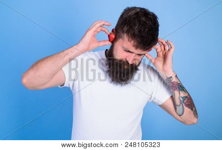Man Bearded Hipster Red Ripe Strawberry Ears As Headphones. Summer Hit Concept. Hipster Beard Listen