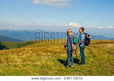 Happy Couple With Walking Poles And Backpacks In The Mountans
