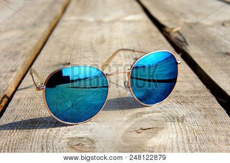 Fashionable Mirror Glasses With Blue Glasses On The Sun Lie On A Wooden Floor Rest Trip Reflected In