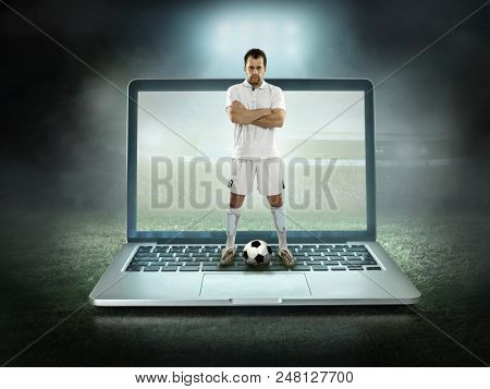 Caucassian soccer Player in stay with ball in a professional sport game play on the laptop in football under stadium lights.