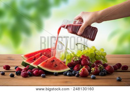 healthy eating, food, dieting and vegetarian concept - hand pouring fruit and berry juice or smoothie from bottle to glass over green natural background