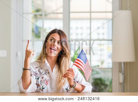 Young woman at home holding flag of united states of america surprised with an idea or question pointing finger with happy face, number one