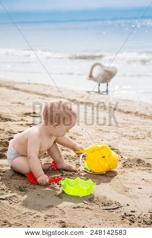 Cute Baby Boy Playing With Beach Toys On The Sand In Summer Vacation. Travel And Adventure Concept.