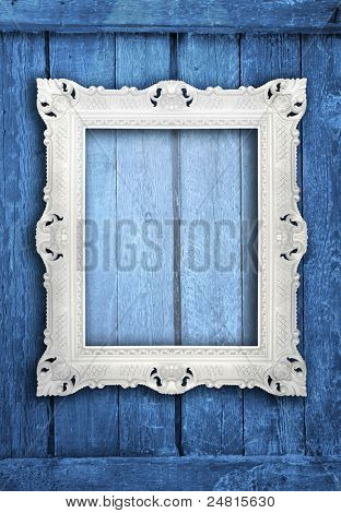 Ornamental white frame on an aged  wooden background
