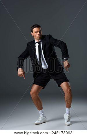 Emotional Stylish Man In Shorts Pointing By Finger On Shorts On Grey Background