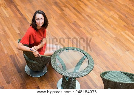 A Girl In A Red Dress Is Sitting At A Coffee Table. The Brunette Sits In The Hall Behind A Glass Tab