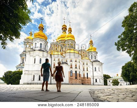 Young Tourist Couple In Silhouette Looking At Church With Golden Domes At Kiev Pechersk Lavra Christ