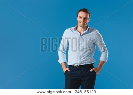 Handsome Man Standing With Hands In Pockets And Smiling At Camera Isolated On Blue