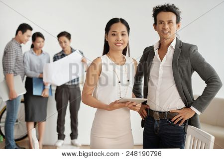 Portrait Of Smiling Business Colleagues With Touchpad Standing At Office