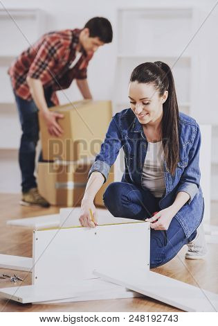 Young Couple Assembling Furniture in New Home. Moving to New House. Relocation to New place. Cardboard Boxes full of Household Things. Repair in Apartment. Starting Life on New Place. poster