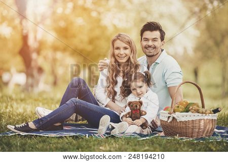 Happy Young Mother And Father With Daughter On Family Picnic On Green Grass In Park On Sunny Summer
