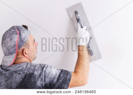 Plasterer applying gypsum plaster on the wall. House renovation concept.