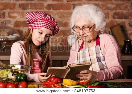Grandmother and her cute granddaughter searching for a recipe in old cooking book poster