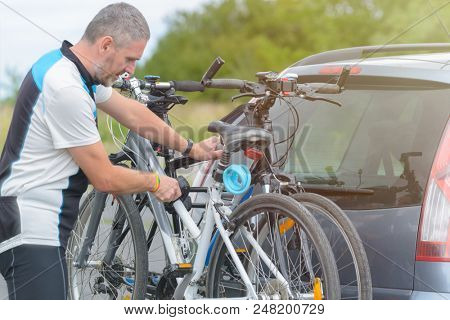 Man wearing sportswear loading bicycles on the bike rack mounted to a car towbar
