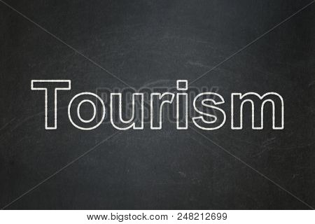 Tourism Concept: Text Tourism On Black Chalkboard Background