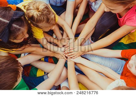 Top View Photo Of Team Of Children Making An Agreement, Putting Their Hands Together. Kids Waving Th