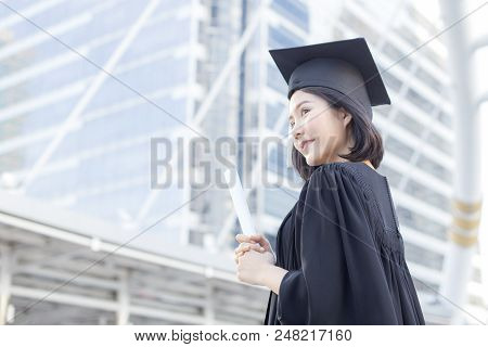 Young Asian Woman Students Wearing Graduation Hat And Gown At University, Woman Students  With Gradu