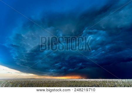 Large, powerful tornadic supercell storm moving over a field in Oklahoma sets the stage for the formation of tornados across Tornado Alley.
