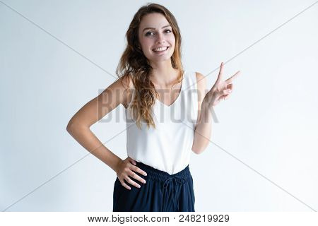 Happy Beautiful Woman Showing Victory Sign And Looking At Camera. Friendly Young Lady. Success Conce