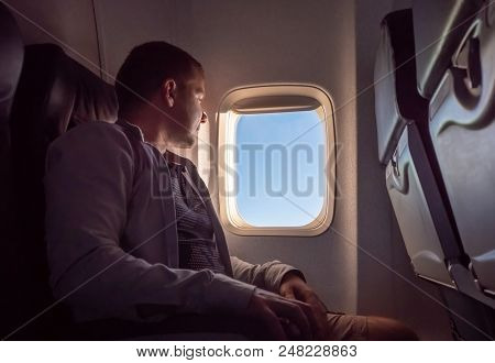 The Young Man Looks Out The Window Of The Plane In The Evening