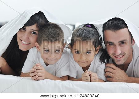 happy young Family in their bedroom have fun and play in bed poster