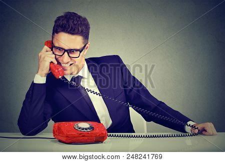 Pushy young salesman business man advertising his best product on a phone poster