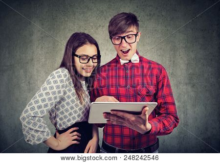 Casual And And Woman In Glasses Exploring Modern Touchpad Looking Super Excited On Gray Background