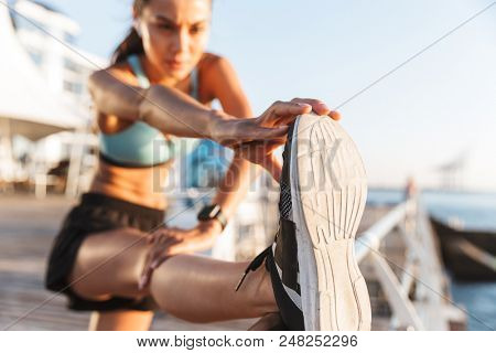 Blurry photo of slim athletic sportswoman 20s in sportswear raising leg on railing and stretching foot during workout on boardwalk at seaside in morning