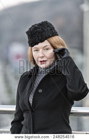 Portrait Of Brunette Lady In Black Coat And Gloves. Lady With Head Black Head Wear. Winter Fashion F
