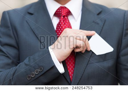 Closeup Of Businessman Hand Holding A Business Card Over Suit Pocket Isolated On White. Businessman