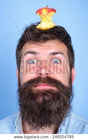Hipster Happy Face With Apple Stump Target On Head Blue Background, Close Up. Man Handsome Hipster L