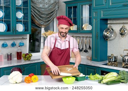 Mustached Handsome Chef In Apron And Cap Puts Mushrooms For Salad Into Green Plate. Mustached Man Co