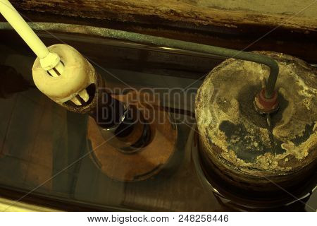 Insides Of Old Toilet Tank, Filled With Water. Fittings And Shut Off Valves