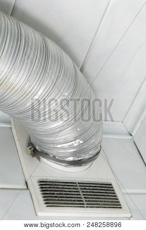 Home Duct Hose. Air Vent Grille White Cover Under Silvery Corrugated Round Wide Aluminium Pipe. With