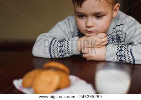 Sad Boy. The Child Looks At The Cookies And Milk With Sadness. Close View.