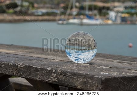 Picnic Table Holding Round Sphere Lens That Shows Ventura Marina Backgound Upside Down.